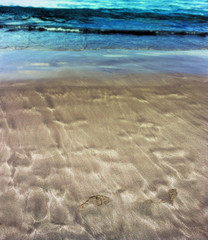 Beautiful patterns from the waves on the sand. Volcanic sand on the beach.  Footprints on sand. Summer
