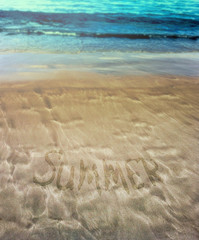 Beautiful patterns from the waves on the sand. Volcanic sand on the beach. Inscription on sand. Summer