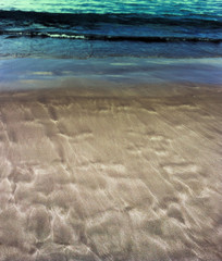 Beautiful patterns from the waves on the sand. Volcanic sand on the beach. Summer
