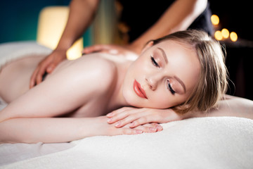 Attractive, young and healthy girl lying on massage bed in spa salon receiving hot stone massage as pleasant bonus to the main Total Body Oriental Massage. Antistress and Refreshment idea