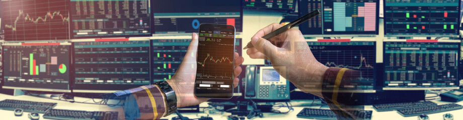 Double exposure of hand holding smartphone with Stock market quotes and chart in monitor computer room with business office equipments .business and money concept, panorama