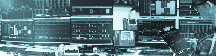 Double exposure of business woman holding blank tablet for Stock market quotes and chart in monitor computer room with business office equipments .business and money trading concept,panorama photo