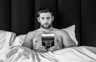 Shirtless sexy hunky man with beard lies in bed reading book