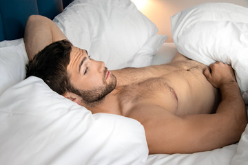 Shirtless sexy hunky man with beard lies naked in bed