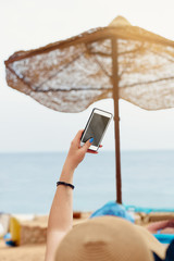 Close up hand holding smartphone on summer beach. technology, travel, tourism, communication and people concept