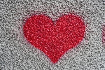 cœur rouge sur mur granuleux de couleur crème