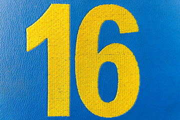 Closeup of woven sixteen 16 number on cloth against bright vibrant blue background sixteen