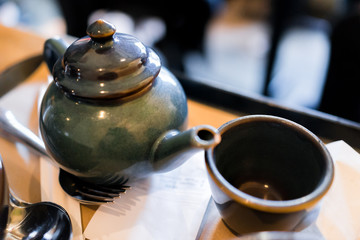 Closeup of teapot, cup in Japanese traditional Asian restaurant or cafe with receipt on tray table, spoon, fork
