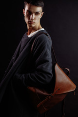 Studio shot of a handsome young male model wearing dark topcoat and brown lether beg over his shoulder on black background. Men Garments and Accessories Concept