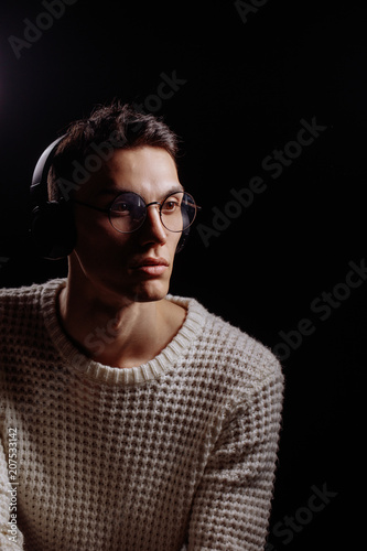 f28c3287c077 Portrait of young artistic musician man in glasses listening to music  through headphones with closed eyes on a black background.