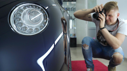 A young professional photographer (a guy, a man) takes pictures of a car in a car salon. Concept: lifestyle, new photo, car, photo apron, flash, exhibition.