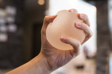 Silicone breast implant on hands