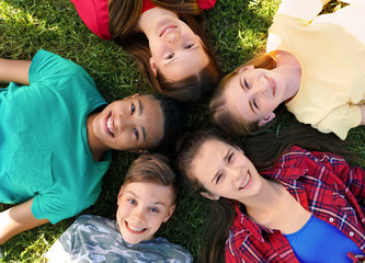 Group of children lying on grass, top view. Summer camp