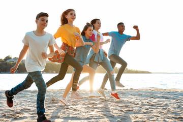 Group of children running on beach. Summer camp