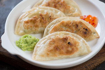 Closeup of pan fried korean potstickers served on a white plate, selective focus