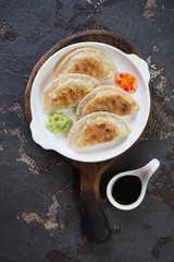 White plate with fried potstickers on a rustic wooden serving board, vertical shot on a brown stone background, top view