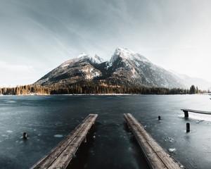 Gefrorener See im Spätwinter in den Alpen mit blick auf gewaltiges Bergmassiv und kleinem Holzsteg im vordergrund im Bild Hintersee und Watzmann