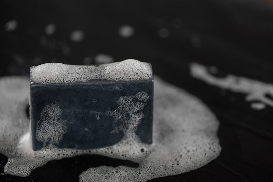 block of natural carbon charcoal soap on black stone background with bubbles