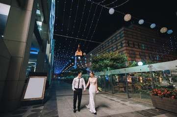 Happy newlyweds stroll through the night city and the evening boulevard. International wedding of Asian and European women. Copy space.