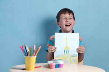 Smiling European boy demonstrating picture he has drawn.