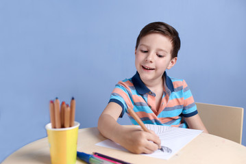 Cheerful smiling Caucasian boy spending time drawing with colorful pencils at home.