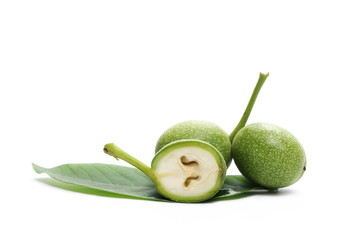 Half green walnut and leaf isolated on white background