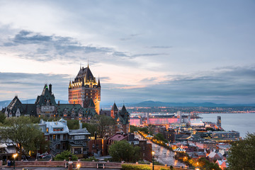 Cityscape or skyline of Quebec City, Canada, Chateau Frontenac, park and old town streets during sunset with illuminated castle, red Espace 400e building