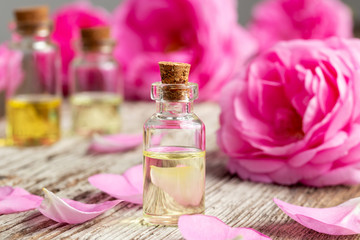 A bottle of essential oil with roses and petals on a wooden background