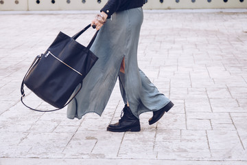street style portrait of an attractive woman wearing a long dress, biker ankle boots and a big black leather tote bag . fashion outfit