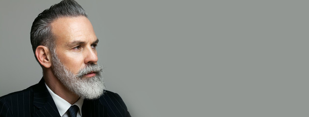 Close-up portrait of bearded gentleman wearing trendy suit over empty gray background. Copy Paste text space. Wide. Wall mural