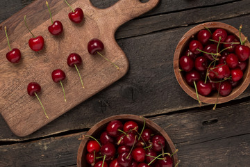 Fresh cherries close up on a wooden board and two plates full of cherries on a wooden table