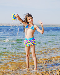 A cool young girl in a swimsuit with long hair flying in the wind watering from a watering can standing in sea water
