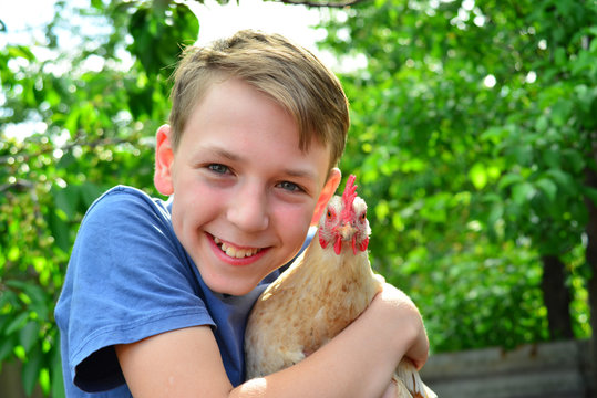 The boy is holding a white chicken and smiling