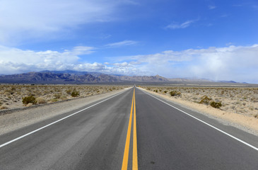 Driving on the open road in the desert with mountain backdrop