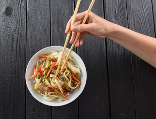 Slender woman hand with chop sticks in bowl of traditional Asian udon noodles on black background minimalist style