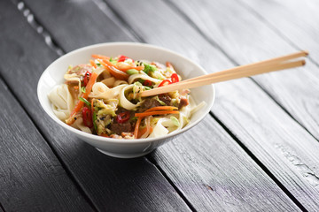 Asian udon noodles with meat in white bowl with chop sticks on black background