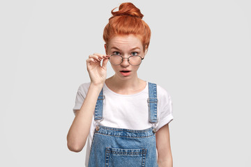 Photo of surprised ginger woman looks scrupulously at camera, reads something printed with small type, wears denim dungaree, isolated over white background. Stupefied redhead female wears glasses