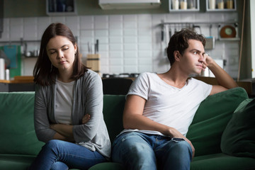 Unhappy millennials ignoring avoiding not talking after fight, frustrated couple in quarrel sitting silent on couch at home having disagreement thinking of misunderstandings in bad relationships