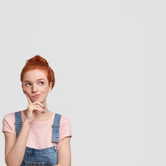 Vertical shot of lovely redhead female being deep in thoughts, curves lips and looks pensively upwards, poses against white blank wall with copy space for your advertising content. Dreamy foxy girl