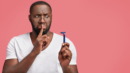 Horizontal shot of African American male makes silence gesture and looks secretly at razor, going to shave his thick beard, stands against pink background with blank space for advertisement.