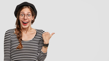 Horizontal shot of amazed Parisian female shows something wonderful, indicates with thumb, demonstrates free space for your advertising content. French woman in stylish clothes expresses surprisement