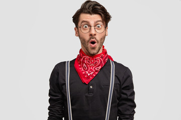 Photo of handsome bearded hipster, keeps mouth wide opened, wonders something, dressed in fashionable clothes, isolated over white background. Unshaven surprised man poses indoor. Emotions concept