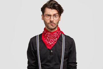 People, facial expressions concept. Portrait of attractive hipster male with trendy hairdo, curves lips, raises eyebrows, dressed in black shirt with red bandana. Attractive man in bewilderment