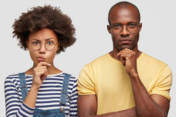 Headshot of puzzled African American husband and his wife hold chin and purse lips, looks with hesitation at camera, think what place for vacation to choose. Young family couple stand indoor