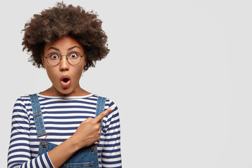 Excited anxious lovely young African female with curly black hair, dark skin, keeps mouth opened, stares with surprisement, points finger in side against white blank wall for your promotional text.