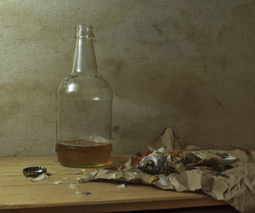 A photograph depicting a bottle of beer. Nearby is the dried fish eaten. Still life