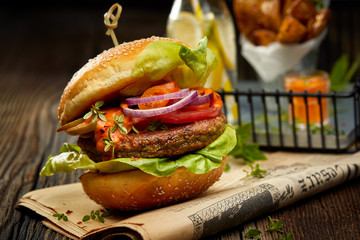 Falafel burger with addition of lettuce, tomato, onion, pickle cucumbers, spicy aromatic sauce and herbs on a wooden rustic table. Vegetarian food tasty and nutritious