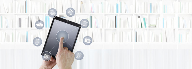 hand touching digital tablet with icons isolated on library background