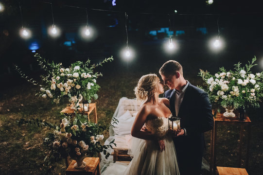 Fashionable newlyweds stand at night against the backdrop of chic decorations and flowers, electric bulbs and garlands, in the backlight. Night shooting of the bride and groom.Floristics.Film effect.