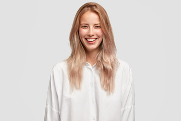 Wall Mural - Cheerful beautiful European female with pleasant smile, has white perfect teeth, wears oversized shirt, has straight hair, laughs on funny joke. People, positive emotions and feelings concept